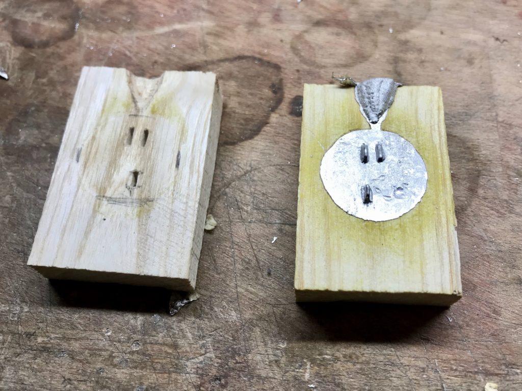Rückseite der kleinen Fibel in der Holzform.